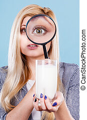 Woman looking at milk through magnifying glass
