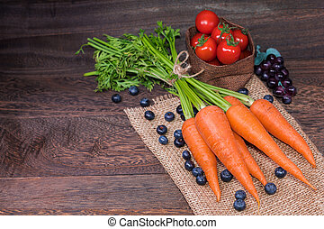 Healthy eating and dieting concept, fresh carrot or organic healthy , tomato ,fruit, vegetables on a grey wooden table wall background