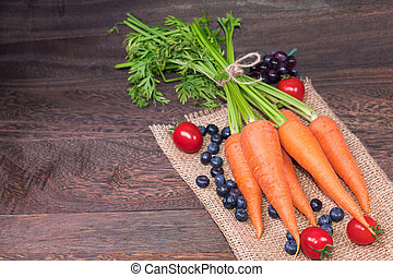 Healthy eating and dieting concept, fresh carrot , tomato and blueberries on a grey wooden table wall background with copy space .