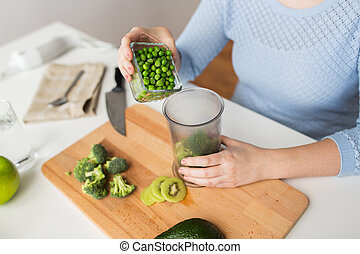 woman hand adding pea to measuring cup - healthy eating, ...