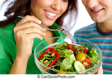 Close-up of young couple eating vegetable salad from glass bowl