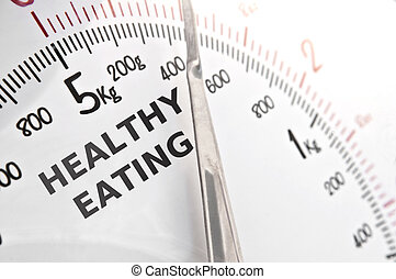Close up on a set of white kitchen scales with the words 'healthy eating' in the dial face