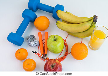 healthy eating concept. Dumbbells, skipping rope, bananas, oranges, measuring tape waist, oranges, red apple, green apple, orange juice on a white table. Fitness diet. view from above