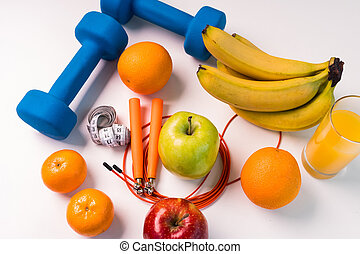 healthy eating concept. Dumbbells, skipping rope, bananas, oranges, measuring tape waist, oranges, red apple, green apple, orange juice on a white table.Fitness diet. view from above