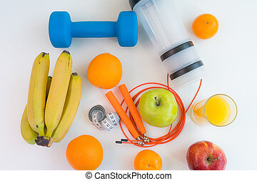 healthy eating concept. Dumbbells, skipping rope, shaker, bananas, oranges, measuring tape waist, oranges, red apple, green apple, orange juice on a white table. Fitness diet. view from above.