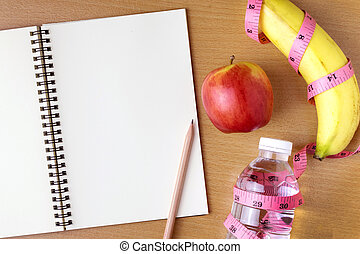 Healthy eating concept, tape measure, fruit and water bottle on a wooden background, blank copy space notebook