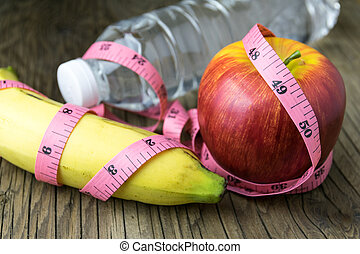 Healthy eating concept, tape measure, fruit and water bottle on a wooden background