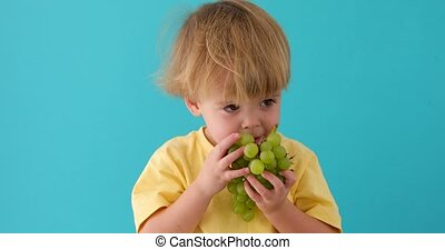 Healthy eating concept with child eating grapes