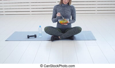 Healthy eating concept. Young Fit woman eating healthy salad...