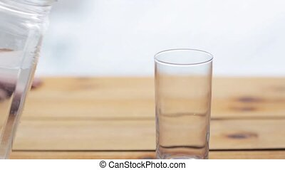 water pouring into glass on wooden table