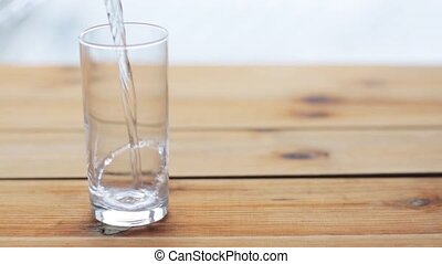 water pouring into glass on wooden table - healthy eating, ...