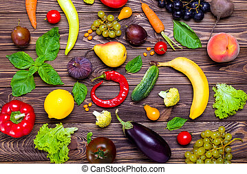 Healthy eating, diet, detox background. Assortment of bright organic fresh fruits and vegetables on the dark wooden table. Vegan, vegetarian, raw food. Top view, selective focus.