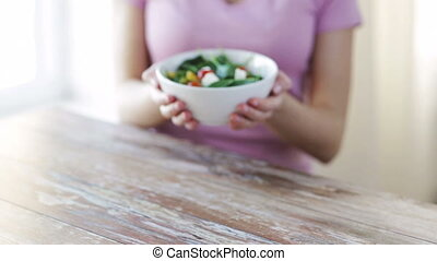 close up of young woman hands showing salad bowl