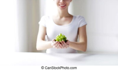 close up of young woman showing green grape bunch
