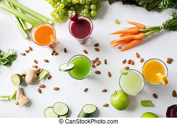 healthy eating, drinks, diet and detox concept - close up of glasses with different fruit or vegetable juices and food on table