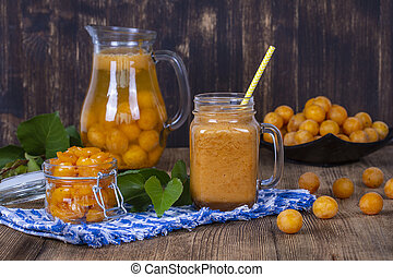 Healthy eating, food, dieting and vegetarian concept - mug glass of juice smoothie shake from yellow plum, lemonade, jam and ripe yellow plum