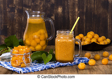 Healthy eating, food, dieting and vegetarian concept - mug glass of juice smoothie shake from yellow plum, lemonade, jam and ripe yellow plum, on wooden table.