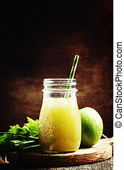 Healthy eating for weight loss: freshly squeezed juice from green apple and celery, vintage wooden background, selective focus