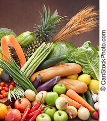 healthy eating - fresh fruits and vegetables against brown ...