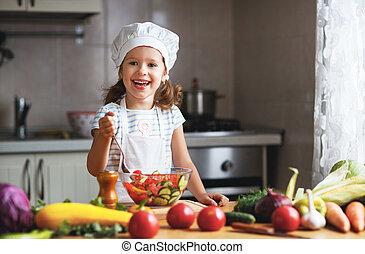 Healthy eating. Happy child girl prepares  vegetable salad in kitchen