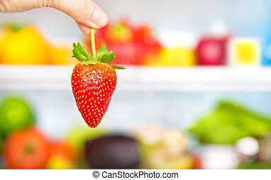 Eating healthy food conceptual background, weight loss and body care concept, fresh strawberry in hands, full fridge of diet nutrition, selective focus
