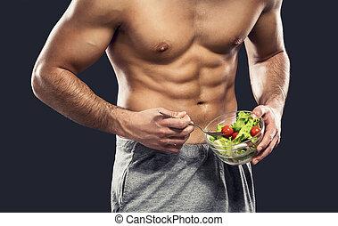Healthy Eating - Muscular man eating a healthy salad,...