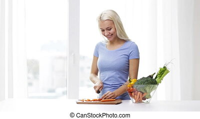 smiling young woman chopping carrot at home - healthy...