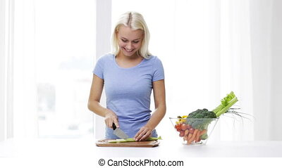smiling young woman chopping celery at home