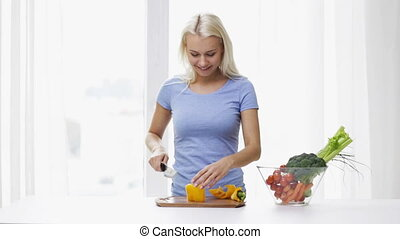 smiling young woman chopping pepper at home