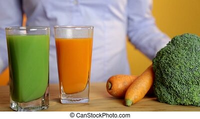 healthy eating, vegetarian food, diet and detox concept - woman hand putting glass of carrot juice on table with vegetables.