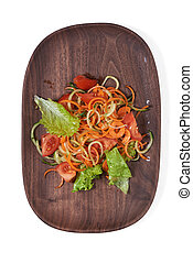 Vegetarian vegetable salad on a wooden plate isolated