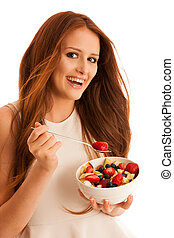 healthy eating  - woman eats a bowl of fruit salad isolated over white background - vegetarian meal