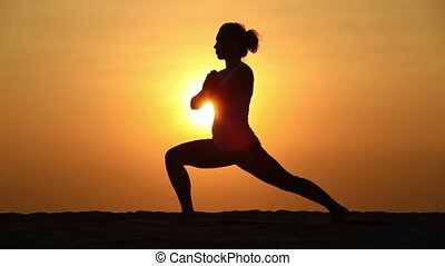 Healthy exercise - Slim woman doing yoga over orange sun