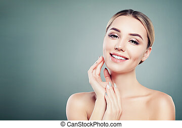 Healthy face young smiling woman on blue background with copy space
