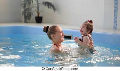 healthy family mother teaching baby swimming pool