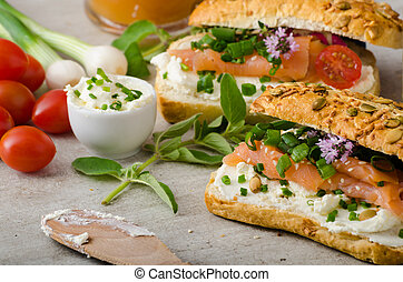 Healthy Fish snack - wholemeal baguette with cream cheese, seeds and smoked salmon with fresh herbs