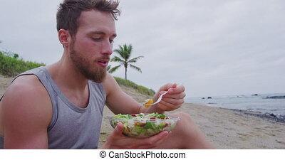 Healthy fit man eating organic vegan food on beach - Fitness...