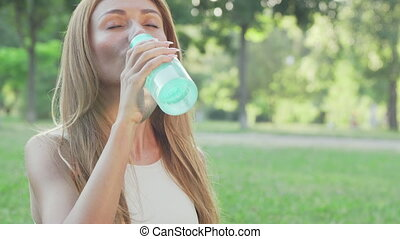 Healthy fit woman drinking water while doing yoga in the...