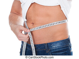 Healthy fit young man measuring his waist with a tape measure to monitor his weight isolated on white