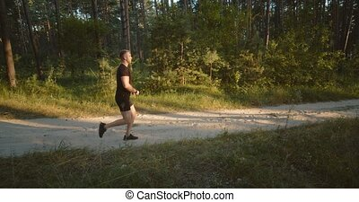 Healthy fitness man in black sport clothing doing cardio outdoors during amazing sunset. Handsome male training regularly to be in good body shape.