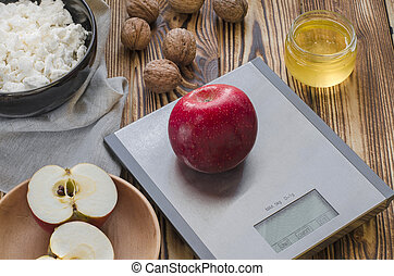 A red apple lies on a metal scale on a wooden table, next to it is a plate with cottage cheese, a plate with a cut apple, nuts lie and a jar of honey