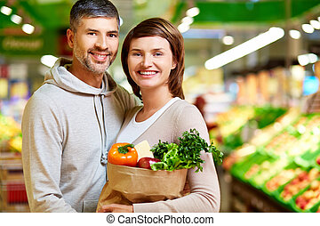 Healthy food eaters - Image of happy couple with paperbag...