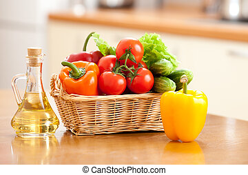Healthy food fresh vegetables in basket and bottle with oil on t