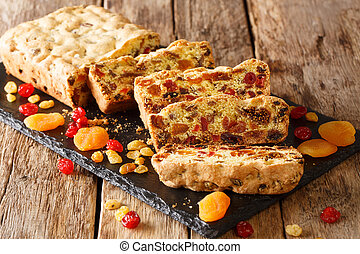 Healthy food fruit cake with dried apricots berries raisins figs cherries closeup on a slate board. horizontal