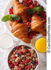 Healthy food: granola, croissants, fresh berries, milk and orange juice close-up on the table. vertical top view
