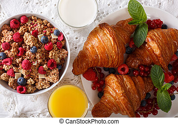 Healthy food: granola, croissants, fresh berries, milk and orange juice close-up on the table. horizontal top view