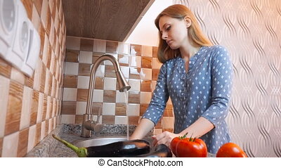 Healthy food lifestyle: beautiful woman casually cooking, washing vegetables at kitchen. Wide shot, handheld.
