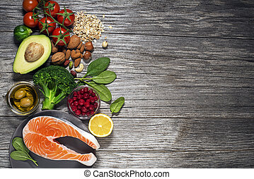 Mixed fresh healthy food on wooden background - heart concept
