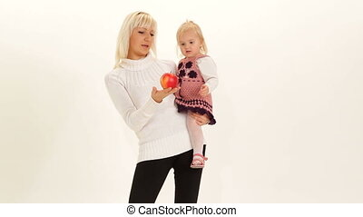 Healthy food - Mother giving an apple to her daughter