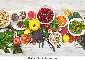 Healthy food selection, clean eating. Fruit, vegetable, seeds, superfood, cereals, leaf vegetable on white background, copy space, top view.